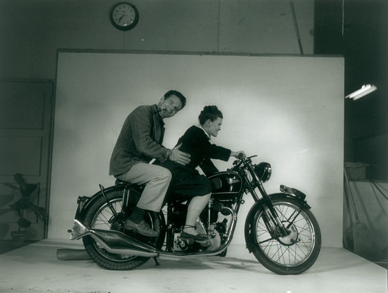 Charles and Ray Eames riding a motorcycle